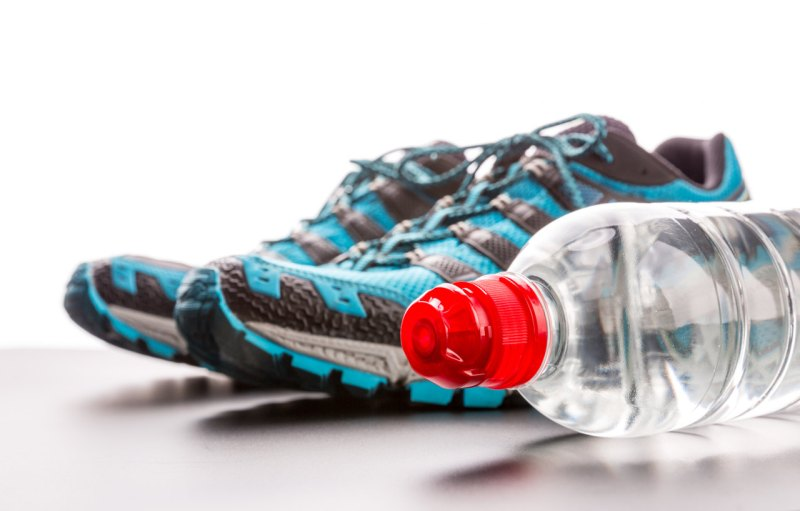 Closeup of blue sports runners and a bottle of water